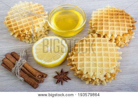 Waffle with cinnamon, badian, honey, lemon on a light wooden background.