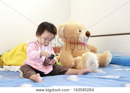 asian baby is playing toys and bear on her bed