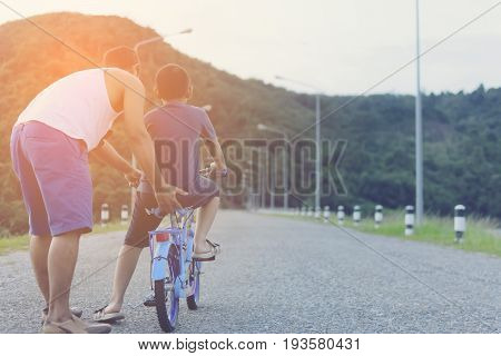 Father and son with bike for starting to the first time of life him.