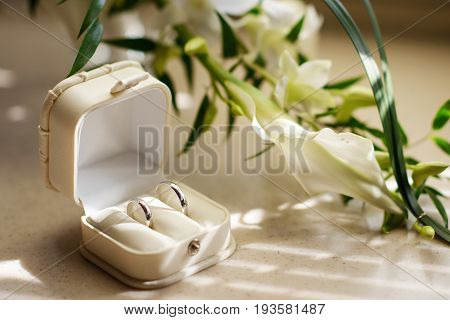 two gold wedding rings in white box with flowers
