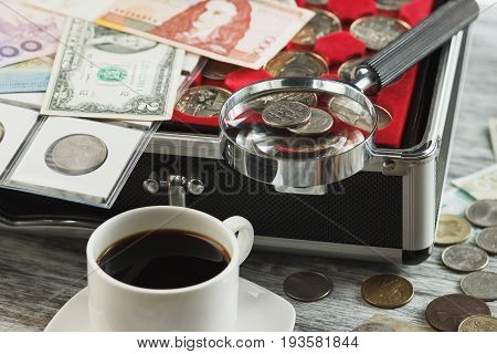 Different Old Collector's Coins And Banknotes With A Magnifying Glass And Cup Of Coffee