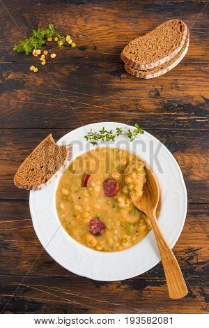 Hearty and healthy split pea and smoked sausage soup with green thyme in a white plate on the wooden table top view.