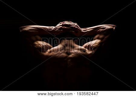Strong muscular man holding his hands behind his head. Perfect shoulders and back muscles. Dramatic light