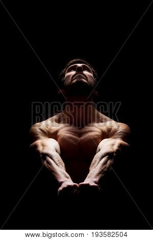 Perfect body and strong mind concept. Muscular man holding his hands together and looking up. Dramatic light.