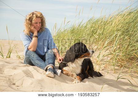 mature woman with her dog on sand and grass sitting
