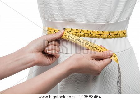 cropped view of dressmaker measuring white dress on dummy isolated on white