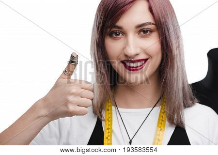 attractive smiling needlewoman with thimble showing thumb up isolated on white