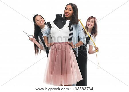 Three Young Fashion Designers Holding Scissors And Measuring Tape While Working With Dress On Dummy