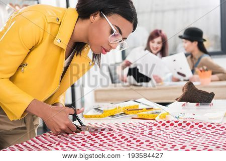 Young Dressmaker In Eyeglasses Cutting Polka Dot Fabric While Her Colleagues Sitting On Background