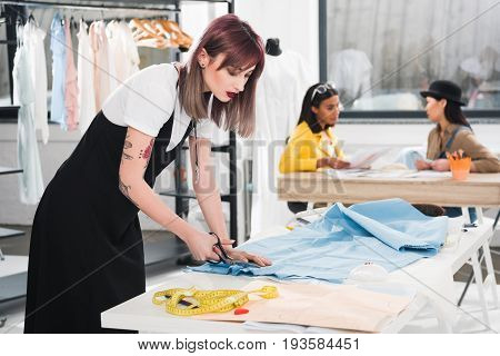 Young Dressmaker Cutting Blue Fabric With Scissors While Her Colleagues Talking On Background