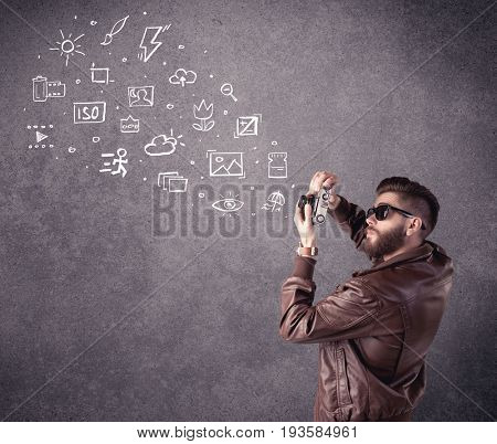 An elegant hipster guy trying to use a vintage camera with camera settings icons drawn on wall, like flash, white balace or ISO value concept
