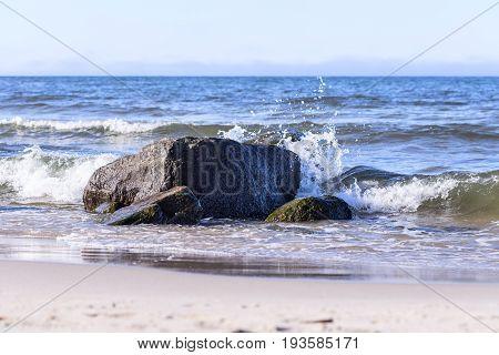 single rock at sea with crashing waves