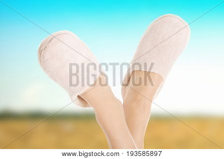Female's feet with white slippers.