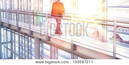 Full length of middle aged businessman walking by railing in modern office