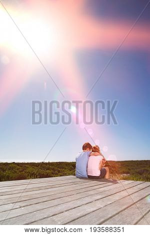 Rear view of young girl and boy sitting on boardwalk