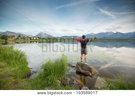 man standing on the rock looking at beautiful view of Hopfensee Fussen Germany