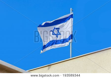 Flag of State Israel waving on roof