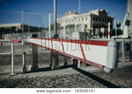 White and red access barrier in horizontal position in a car park entrance.