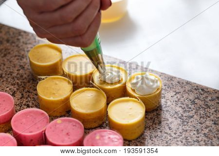 Woman Hand Decorating Mini Cakes