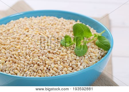 bowl of pearl barley on beige place mat - close up