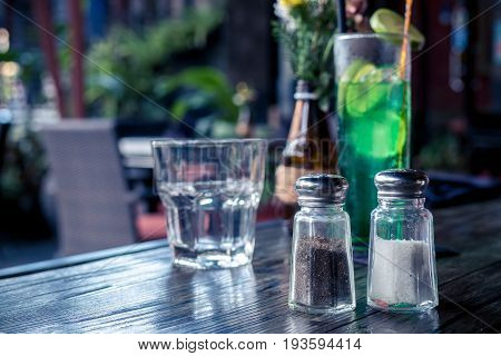 Glass salt and pepper shakers on wooden table in cafe.