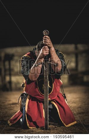 Medieval knight kneeling with sword after battle