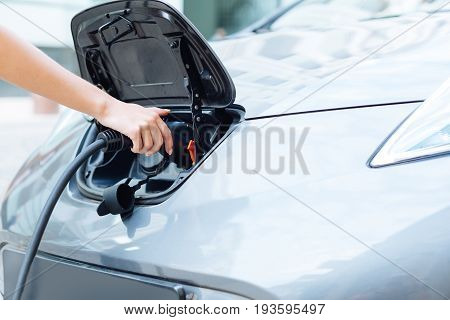 Environment conscious. Beautiful dainty female hands holding an electrical nozzle and charging a state-of-the-art electric car