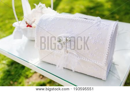 Decorative paper chest with laces on wedding ceremony. Cute tradition to collect money presents in symbolic chest. Wedding set up outdoors in park.