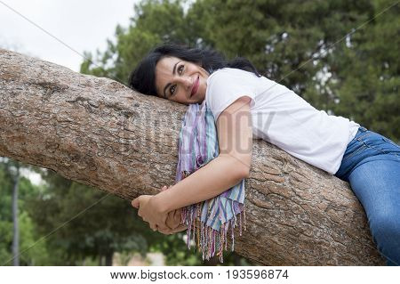 Pretty Attractive Woman Wearing Causal Clothes And Hugging A Tree In A Green Park