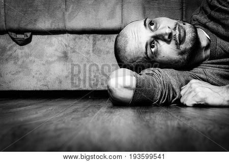 Depression. Depressed and lonely man lying on the floor of his home. Black and white.