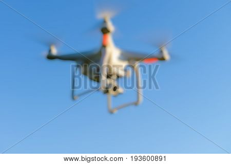 Abstract blur drone quad copter with digital camera flying in the blue sky for background