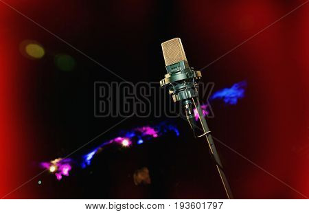 Microphone oncolor background. Retro microphone. A microphone on stage. A pub. Bar. Restaurant. Classic. Evening. Night show. European restaurant. European bar. American restaurant. American bar.