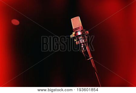 Microphone on red background. Retro microphone. A microphone on stage. A pub. Bar. Restaurant. Classic. Evening. Night show. European restaurant. European bar. American restaurant. American bar.