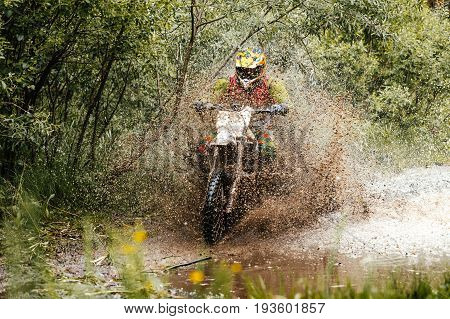 athlete bike enduro riding puddle of water and mud in forest