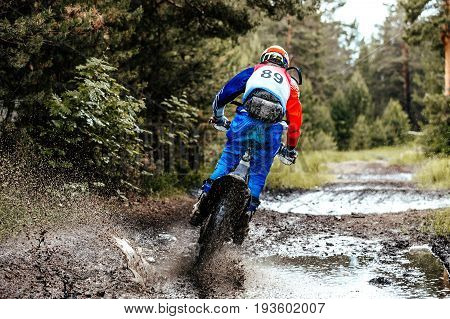 back motocross enduro athlete puddle of mud and water in forest