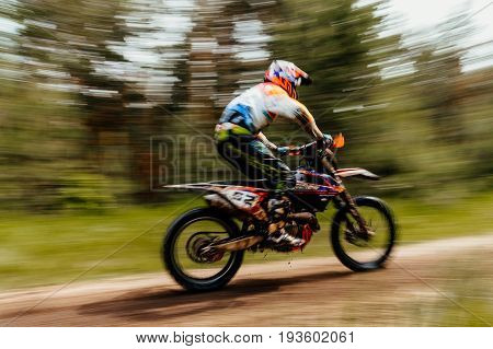 blurred motion athlete bike enduro in forest trial racing motocross