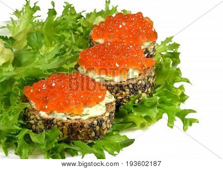 Small sandwiches of black baguette, sprinkled with grains of cereals and poppy, with red caviar and butter, shot down with finely chopped dill, lie on green leaves of crispy salad