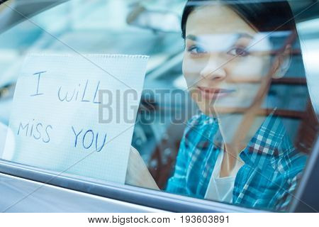 Heartbreaking farewells. The close up of a gorgeous young woman pressing a note saying I will miss you to the car window while departing