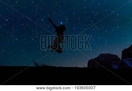 Silhouette of young woman jumping over sand hill beneath the stars Milky Way and a lot of stars over the mountain at Wadi Rum desert. Concept for happiness travlling and freedom.