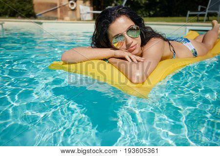 Enjoying suntan. Vacation concept. Slim young woman in bikini on the yellow air mattress in the swimming pool.