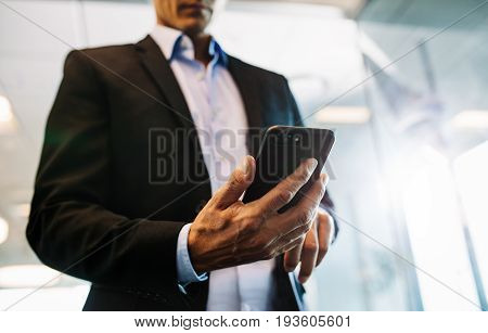 Close up of male hands reading ext message on smart phone. Businessman man hand using mobile phone in office.