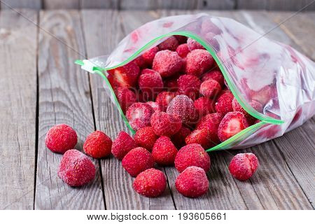 Frozen strawberries in a bag on a wooden background