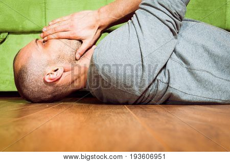 Depression. Depressed and lonely man lying on the floor with hands on his face.