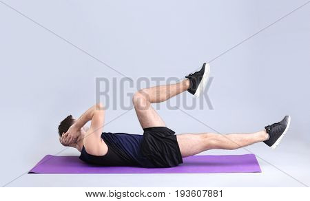 Young man doing bicycle crunch exercise on white background
