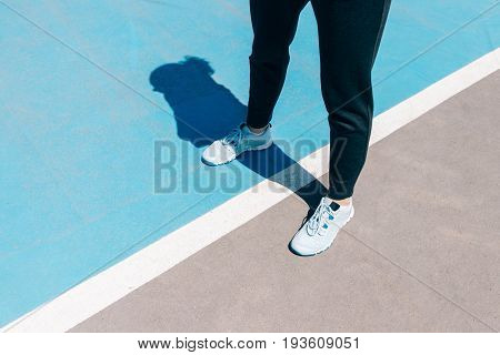 Cropped Image Of Female Legs In Sneakers And Black Pants Standing On A Blue Sports Field