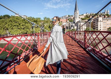 Young and stylish businesswoman walking on the red footbridge in the old town of Lyon city in France