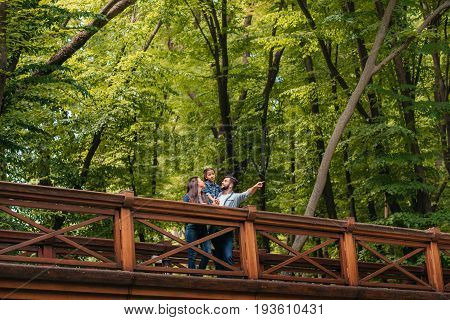Young Interracial Family Standing On Wooden Bridge, While Father Pointing Somewhere Into The Forest