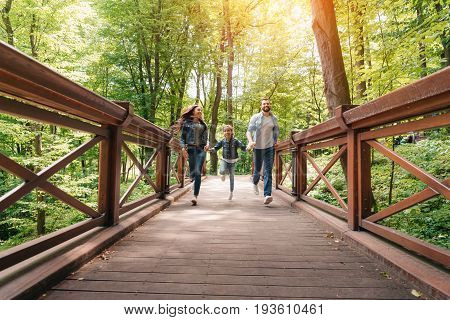 Young Happy Interracial Family Running Through The Wooden Bridge In Sunny Forest