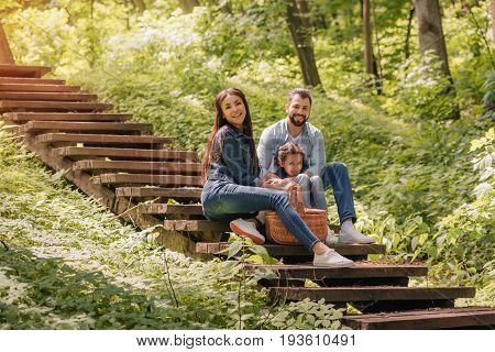Young Smiling Interracial Family With Picnic Basket Sitting On Wooden Stairs In Sunny Forest