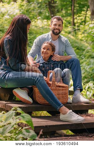 Young Happy Interracial Family With Picnic Basket Sitting On Wooden Stairs In Sunny Forest